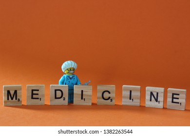Word MEDICINE written with Scrabble letters with Lego mini figure od doctor next to it. Concept of medical help. Editorial photo, macro photography, studio shot isolated on orange background.