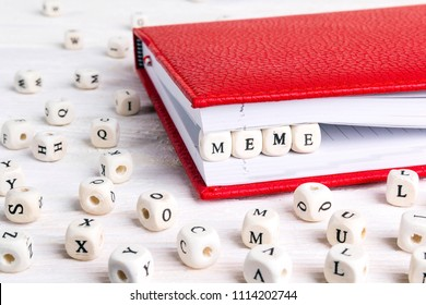 Word Meme written in wooden blocks in red notebook on white wooden table. Wooden abc.