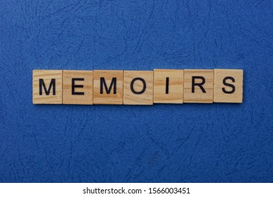word memoirs made from brown wooden letters lies on a blue table