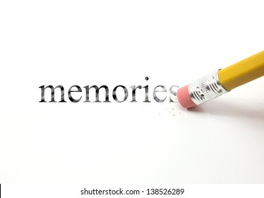 The word memories written with a pencil on white paper.  An eraser from a pencil is starting to erase the word memories.