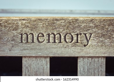 The word memory carved into a wooden bench