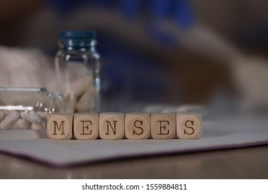 Word MENSES composed of wooden dices. Pills, documents and a pen in the background. Closeup