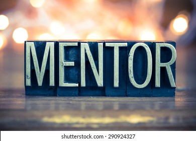 The word MENTOR written in vintage metal letterpress type on a soft backlit background.