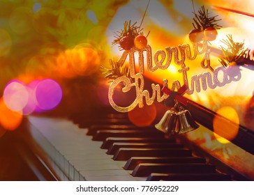 word Merry Christmas hanged over piano Keys music instrument with colorful Bokeh light effected