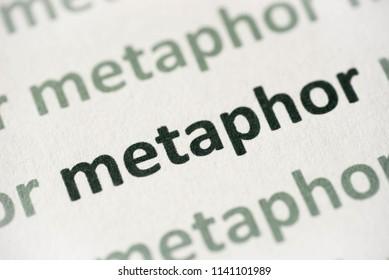 word metaphor printed on white paper macro