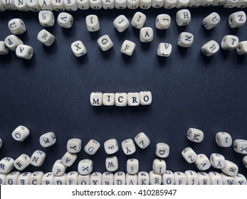 Word Micro of small white cubes next to a bunch of other letters on the surface of the composition on a dark background