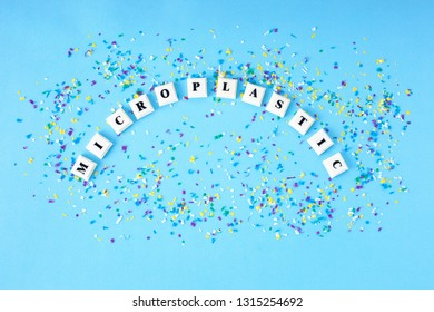Word MICROPLASTIC around small plastic particles on a blue background. Microplastic in water and food. Global ocean pollution. Microplastic problem. Danger to people and the environment.