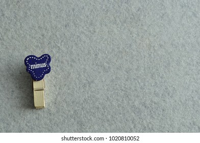 The word minus on a peg isolated on a white background