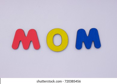 Word Mom from wooden letters on light grey background