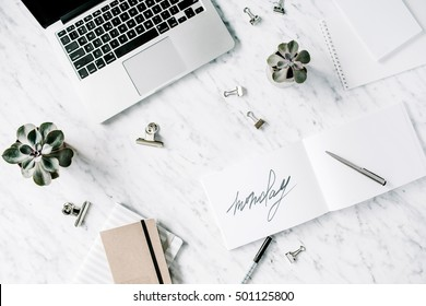 Word monday. Flat lay, top view office table desk. Workspace with laptop, diary, succulent and clips on marble background.