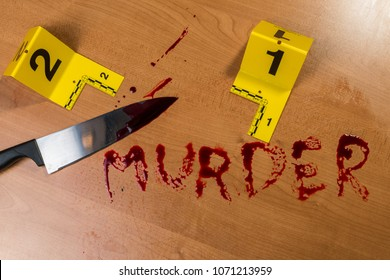 """The word """"murder"""" written in blood with a knife and evidence markers"""