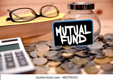 Word Mutual Fund on mini chalkboard with blurred background of books, calculator, reading glass and empty jar. Selective focus. Financial Concept.