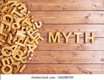 Word myth made with block wooden letters next to a pile of other letters over the wooden board surface composition