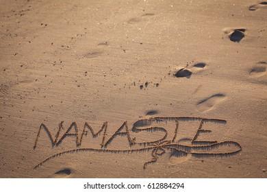 The word namaste written on sand at a beach