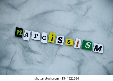 Word narcissism of cut letters on gray background. Psychology concept. A word writing text narcissism. Headline narcissism