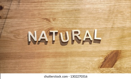 The word natural being spelled by wood letters on a wood surface with real sunlight.