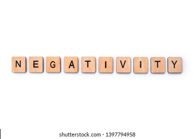 The word NEGATIVITY, spelt with wooden letter tiles over a plain white background.