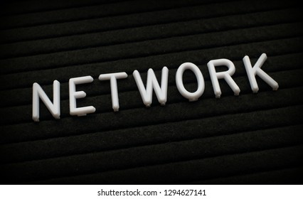 The word Network in white plastic letters on a black letter board