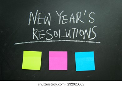 The word New Year's resolution written on the blackboard with blank notes