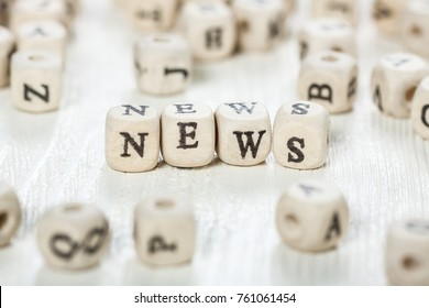 Word NEWS formed by wood alphabet blocks. On old wooden table.