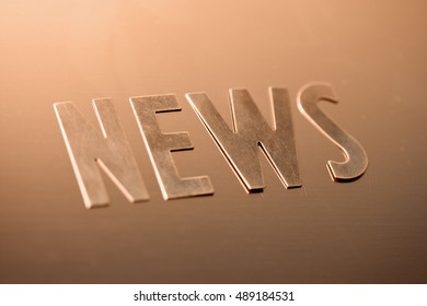 "the word ""NEWS"" on a copper background"