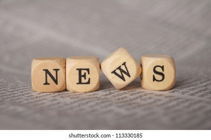the word news on cubes on a newspaper