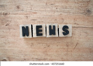 Word news wrote in raw cardboard alphabet stamp in wood background. Rustic alphabet stamp with black letters.