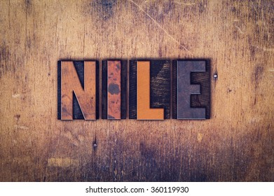 "The word ""Nile"" written in dirty vintage letterpress type on a aged wooden background."