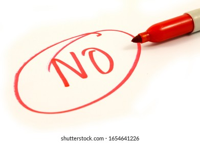 The word NO is boldly written in red marker ink over a white piece of paper.