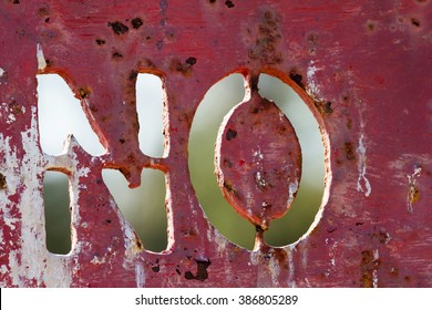 The word NO cut and stenciled into a red weathered and rusty metal sign.
