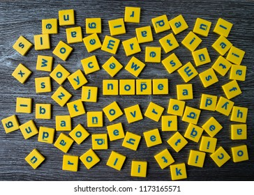 Word Nope among the blocks of English letters scattered. English alphabet letters spread creating concept of saying no or being negative.