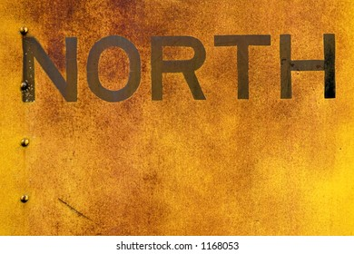 The word North is old and faded and painted on the side of a old train car.