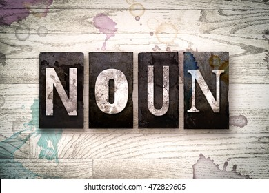 "The word ""NOUN"" written in vintage dirty metal letterpress type on a whitewashed wooden background with ink and paint stains."