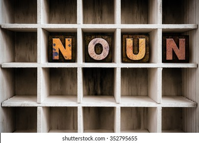 "The word ""NOUN"" written in vintage ink stained wooden letterpress type in a partitioned printer's drawer."