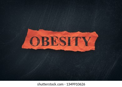 Word Obesity on red torn piece of paper. Close up.