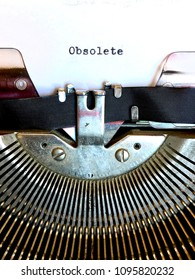 The word OBSOLETE typed in black ink on white paper on vintage manual typewriter machine