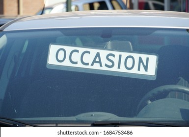 The word Occasion behind the windshield of a car outside a garage, indicating the car is for sale.