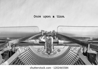 the word once upon a time typed on a vintage typewriter on a sheet of paper. writer, journalist.