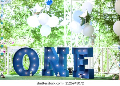 Word One on grass as decor for baby's first birthday celebration. Horizontal color photography.