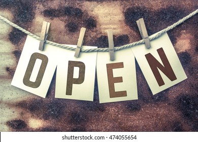 """The word """"OPEN"""" stamped on cards and pinned to an old piece of twine over a rusted metal background."""