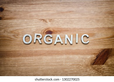 The word organic spelled out by wood letters on a wood surface.