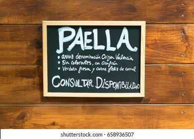 Word paella and its characteristics written on a small blackboard on wooden background.