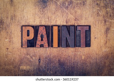 "The word ""Paint"" written in dirty vintage letterpress type on a aged wooden background."