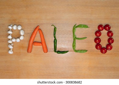 The word 'Paleo' written with fresh vegetables on a wooden background.