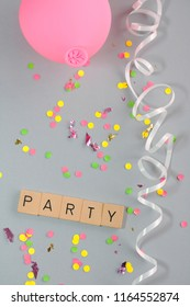 Word PARTY on wooden letters and decoration with streamer, pink balloon and confetti