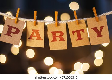 The word PARTY printed on clothespin clipped cards in front of defocused glowing lights.