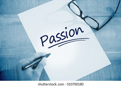 The word passion against left hand writing on white page on working desk