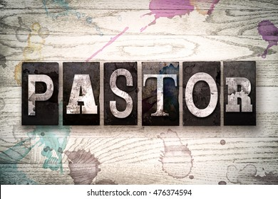 "The word ""PASTOR"" written in vintage, dirty metal letterpress type on a whitewashed wooden background with ink and paint stains."