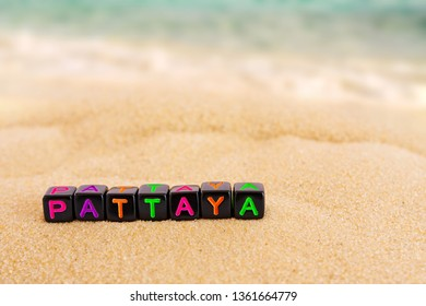 The word Pattaya (resort name in Thailand in English) is made up of colored letters on black cubes on sand with a blurry sea in the background