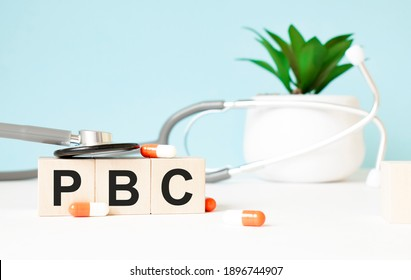 The word pbc is written on wooden cubes near a stethoscope on a wooden background. Medical concept